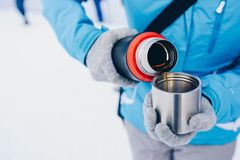 Woman pours hot tea or coffee from metal thermos Stock Image