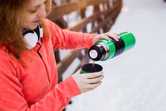 Woman pours hot tea in a mug from thermos. Winter evening Stock Images