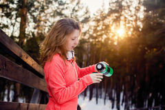 Woman pours hot tea into a mug from a thermos. Winter evening in the Park Royalty Free Stock Photo