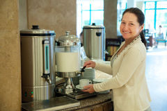 Woman pours milk to coffee Royalty Free Stock Photo