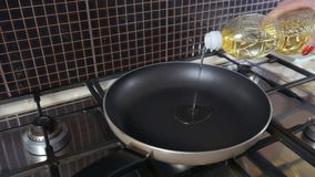 Woman pours oil at the frying pan
