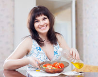 Woman pours oil to veggie salad Royalty Free Stock Photos
