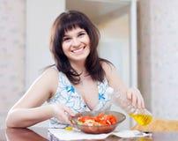 Woman pours oil to veggie salad Royalty Free Stock Photos