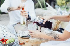 Woman pours red wine into glass. Couple outdoors in chic and beautiful picnic. Hipster men opens bottle of white wine, women with tattoos pours red wine into royalty free stock photos
