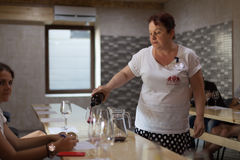 Woman pours red wine into glasses for tasting Royalty Free Stock Image