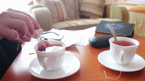 Woman pours tea for a business lunch. Woman holding a teapot with boiling water and brew the tea in white circles. On the table lay a paper, glasses, tablet with stock footage