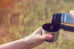 Woman pours water from a thermos flask into a metal mug Light leaks style. Royalty Free Stock Photos