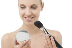 Woman with powder brush and mirror Stock Photography