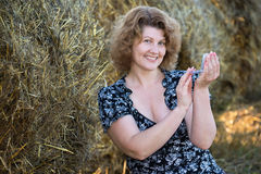 Woman powder oneself in field on a background of straw bales Royalty Free Stock Photos