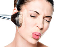 Woman with powder on the skin of cheek. Face of a woman with powder on the skin of cheek- isolated on white royalty free stock photography