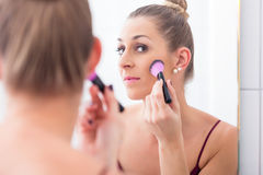 Woman powdering her face with cosmetic brush royalty free stock photos