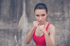 Woman power, self defence concept. Close up portrait of attracti. Ve serious fit boxer, ready for fight, on concrete wall background, wearing pink fashionable Royalty Free Stock Photos