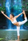 Woman Practacing Yoga in front of Beautiful Waterfall Stock Photo