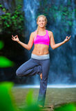 Woman Practacing Yoga in front of Beautiful Waterfall Royalty Free Stock Photography