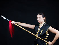 Woman  practice kung fu. Woman practicing  martial art kungfu with weapon in black background Stock Images