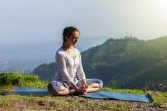 Woman practice yoga asana Baddha Konasana outdoors. Sporty fit woman practices yoga asana Baddha Konasana - bound angle pose outdoors in Himalayas mountains in Stock Image