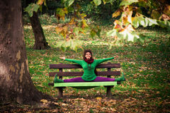 Woman practice yoga on bench in the park Royalty Free Stock Photo