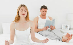 Woman practice yoga while her husband is reading Stock Photo