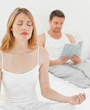 Woman practice yoga while her husband is reading Royalty Free Stock Photography