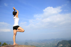 Woman practice yoga at mountain peak Stock Photos