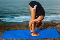 Woman practice yoga on a Rock Above the Sea. Royalty Free Stock Photo