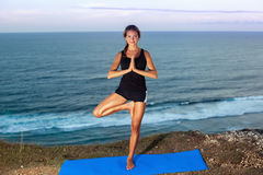 Woman practice yoga on a Rock Above the Sea. Royalty Free Stock Images