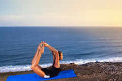 Woman practice yoga on a Rock Above the Sea. Stock Photography