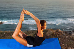 Woman practice yoga on a Rock Above the Sea. Stock Image