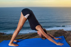 Woman practice yoga on a Rock Above the Sea. Stock Photo
