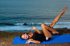 Woman practice yoga on a Rock Above the Sea. Stock Images