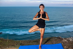 Woman practice yoga on a Rock Above the Sea. Royalty Free Stock Image