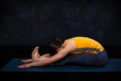 Woman practices Ashtanga Vinyasa yoga asana Paschimottanasana. Woman doing Ashtanga Vinyasa Yoga back bending asana Paschimottanasana - seated forward bend on Stock Image
