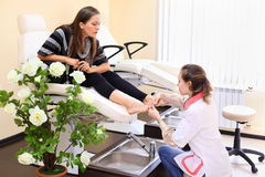 Woman practices chiropody taking care of feet Royalty Free Stock Photos