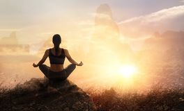 Woman practices meditating yoga at is an asana on a stone, sunse Stock Photo