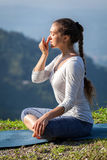 Woman practices pranayama in lotus pose outdoors Royalty Free Stock Photos