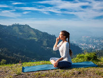 Woman practices pranayama in lotus pose outdoors Stock Photo