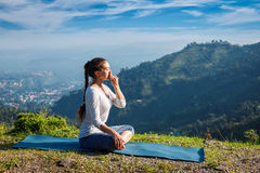 Woman practices pranayama in lotus pose outdoors Royalty Free Stock Photography
