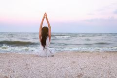 Free Woman Practices Yoga And Meditates In The Lotus Position On The Beach Stock Images - 120813104