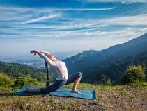 Woman practices yoga asana Anjaneyasana outdoors Stock Images