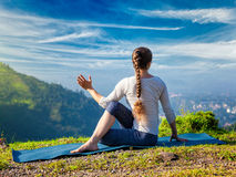 Woman practices yoga asana Marichyasana. Sporty fit woman practices yoga asana Parivrtta Marichyasana - seated spinal twist outdoors in mountains in the morning stock image