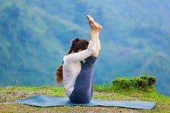 Woman practices yoga asana Urdhva mukha paschimottanasana Royalty Free Stock Photos
