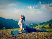 Woman practices yoga asana Urdhva Mukha Svanasana outdoors Royalty Free Stock Photos