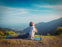 Woman practices yoga asana Urdhva Mukha Svanasana outdoors Stock Photo