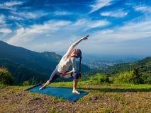 Woman practices yoga asana Utthita Parsvakonasana outdoors Royalty Free Stock Photos