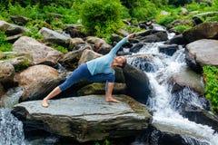 Woman practices yoga asana Utthita Parsvakonasana outdoors Royalty Free Stock Images