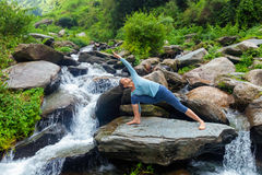 Woman practices yoga asana Utthita Parsvakonasana outdoors Royalty Free Stock Photo