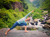 Woman practices yoga asana Utthita Parsvakonasana outdoors Stock Photography