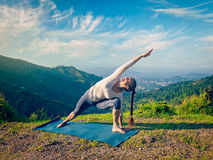 Woman practices yoga asana Utthita Parsvakonasana outdoors Royalty Free Stock Photos