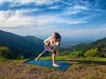 Woman practices yoga asana Utthita Parsvakonasana Royalty Free Stock Photos