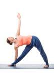 Woman practices yoga asana utthita trikonasana Stock Photography